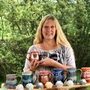 Woman Displays Handmade Ceramic Mugs