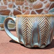 Carved Mug with Blue Glaze in front of a mosaic wall